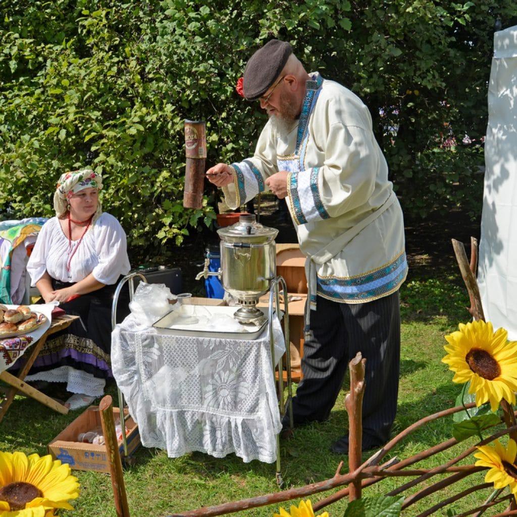 Пожилой мужчина разжигает самовар на ярмарке народного творчества