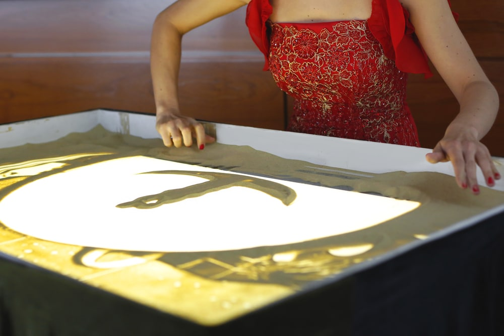 девушка рисует песком